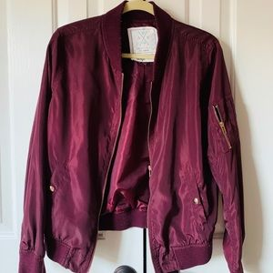 Maroon bomber jacket with gold zippers
